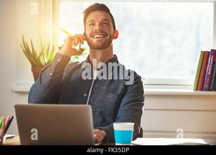 Confident entrepreneur chatting on a mobile phone while working at his desk looking up into the air with an elated - Stock Photo