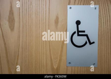 Metal disabled toilet sign on wooden door. - Stock Photo