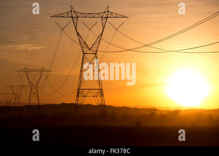 High tension power lines and the setting sun in the Sonoran Desert, California, USA - Stock Photo