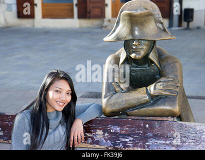 Asian tourist woman sitting on bench with Napoleon soldier at the Main square, Bratislava, Slovakia - Stock Photo