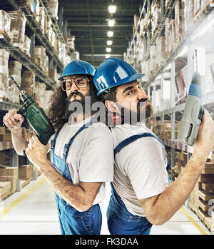 Portrait of two builders in a warehouse - Stock Photo