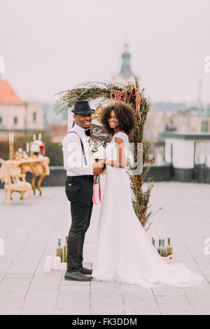 Happy african bride and groom posing for camera smiling on the rooftop - Stock Photo