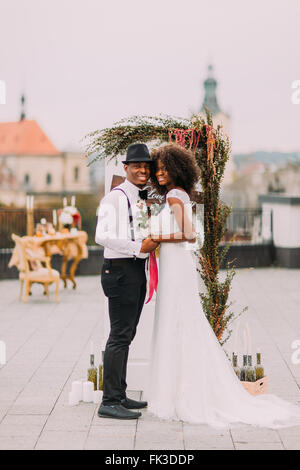 Cheerful black bride and groom holding hands on the wedding ceremony on rooftop - Stock Photo