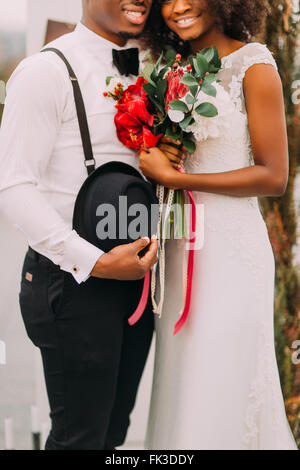 Young pretty black bride and groom happily smiling and holding a bouquet in half length - Stock Photo