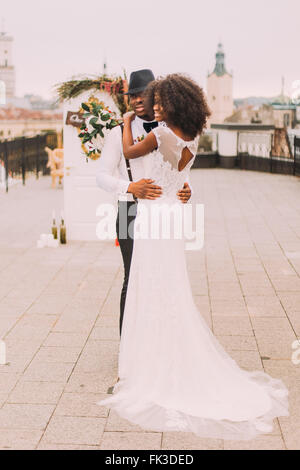 Gorgeous african bride in white lace wedding dress happy in the arms of her groom - Stock Photo