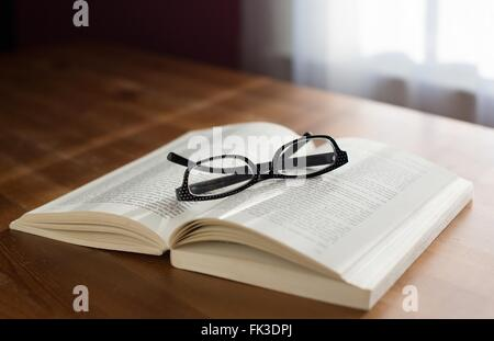 A pair of glasses on top of a book. - Stock Photo