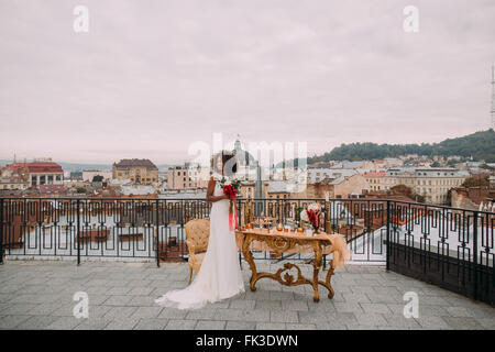 Pretty african bride with wedding bouquet in hands standing on the terrace - Stock Photo