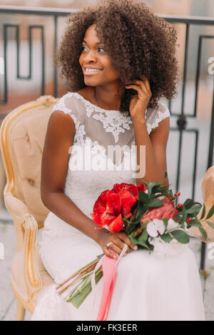 Charming african bride sitting on vintage terracotta chair and happily smiling - Stock Photo