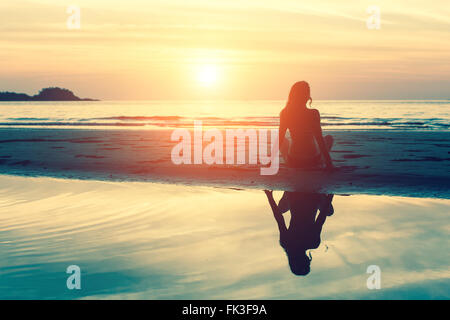 Young woman sitting on the beach, silhouette at sunset. - Stock Photo