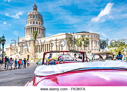 Old convertible American pink car parked in front of El Capitolio. The area is famous for the old American car working - Stock Photo