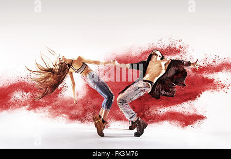Talented young dancers sprinkling red sand - Stock Photo