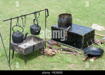 Napoleonic wars re-enactment. Napoleonic 18th century army field kitchen. Two kettles hanging over fire-pan and - Stock Photo