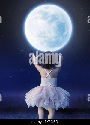 Cute baby girl reaching to the moon - Stock Photo