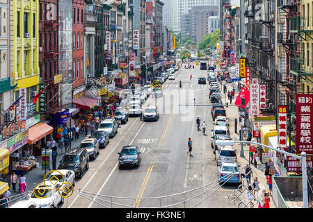 NEW YORK CITY - JULY 2015: Tourists shop at businesses along a busy street in historic Chinatown during 4th of July - Stock Photo