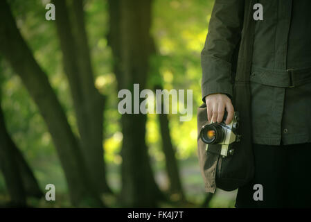 Hipster female photographer exploring spring nature landscapes and making photos of beautiful season scenery with - Stock Photo
