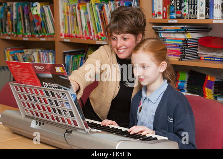 A pupil in school uniform at a Primary School in the UK playing an electronic piano keyboard with a music teacher. - Stock Photo