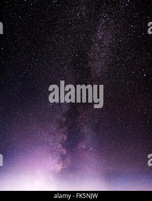 Part of a night sky with stars and Milky Way over violet clouds - Stock Photo