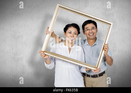 Composite image of older asian couple with frame - Stock Photo
