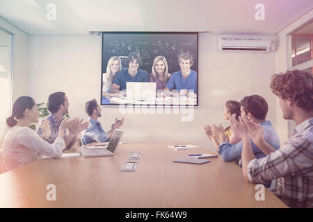 Composite image of a group of students with a laptop look into the camera - Stock Photo