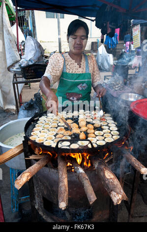 Woman frying tiny chickpea and quails egg fritters on a street market food stall in Pyin Oo Lwyn, Mandalay Division, - Stock Photo