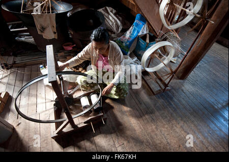 Woman spinning silk thread on a spinning wheel with bicycle wheel, Ko Than hlaing Weaving, Inpawkhan, Inle Lake, - Stock Photo