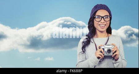 Composite image of asian woman holding digital camera - Stock Photo