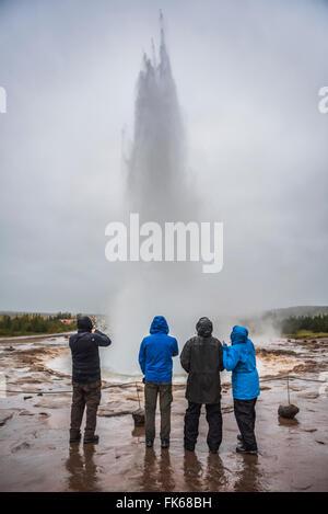Tourists watching Strokkur Geyser erupt, Geysir, The Golden Circle, Iceland, Polar Regions - Stock Photo