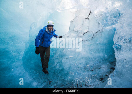 Tourist exploring an ice cave on Breidamerkurjokull Glacier, Vatnajokull Ice Cap, Iceland, Polar Regions - Stock Photo