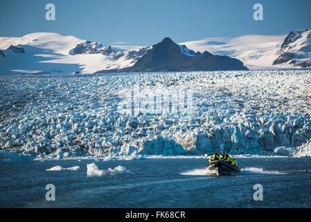 Zodiac boat tour on Jokulsarlon Glacier Lagoon, with Breidamerkurjokull Glacier and Vatnajokull Ice Cap behind, - Stock Photo
