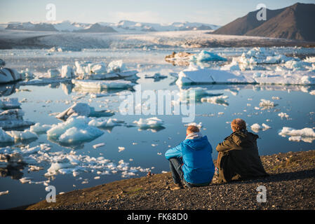 Father and son on holiday at Jokulsarlon Glacier Lagoon at sunset, South East Iceland, Iceland, Polar Regions - Stock Photo