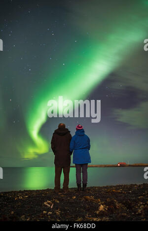 Couple watching the Northern Lights (Aurora Borealis), Reykjavik, Iceland, Polar Regions - Stock Photo