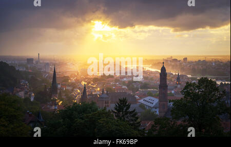 Golden afternoon sun breaking through rain clouds over the spires of Heidelberg Old Town, Baden-Wurttemberg, Germany - Stock Photo