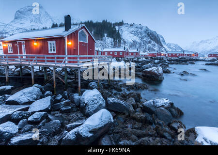 Typical fishermen houses called rorbu in the snowy landscape at dusk, Nusfjord, Nordland County, Lofoten Islands, - Stock Photo