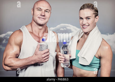 Composite image of portrait of confident athlete man and woman with water bottle - Stock Photo