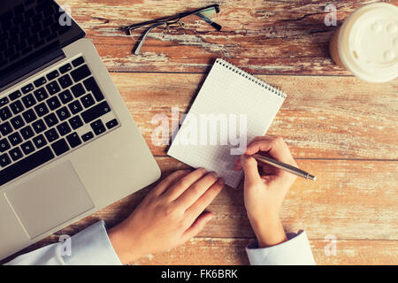 close up of female hands with laptop and notebook - Stock Photo