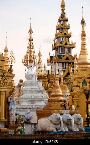 Shrines and pagodas at Shwedagon Pagoda, 2500 year old sacred Buddhist site, covered in gold, in evening light, - Stock Photo