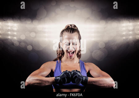 Composite image of aggressive female boxer flexing muscles - Stock Photo