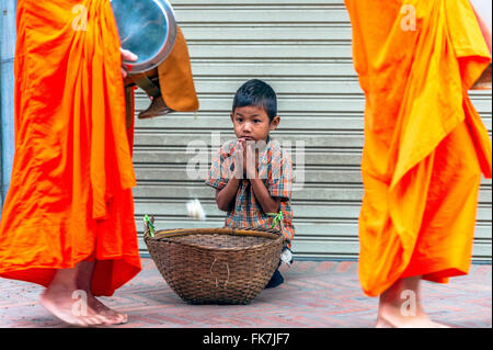 Asia. South-East Asia. Laos. Province of Luang Prabang, city of Luang Prabang, Poor little boy collecting alms from - Stock Photo