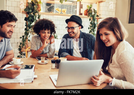 Group of friends hanging out in a coffee shop with a laptop amongst them. Happy young people sitting at restaurant - Stock Photo