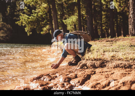 Side portrait of senior male hiker sitting by a lake and putting hands in water. Mature man washing face in lake. - Stock Photo