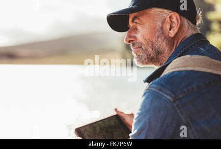 Close up portrait of mature man wearing cap sitting at a lake and looking at a view. Senior caucasian man with beard. - Stock Photo