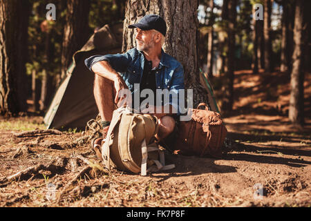Portrait of senior man sitting under a tree with a backpack. Mature man sitting alone at campsite in forest. - Stock Photo