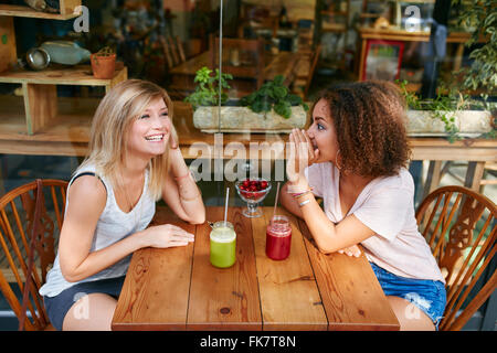 Young female friends having private gossips at sidewalk cafe. Two young women gossiping and whispering outdoors - Stock Photo
