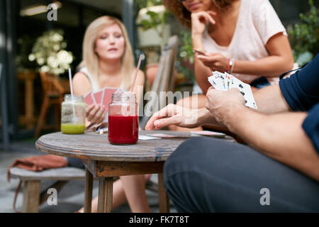 Cropped shot of young friends sitting at outdoor cafe playing card game. Players holding the cards while sitting - Stock Photo