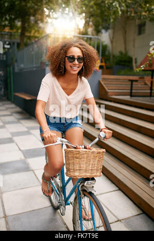 Shot of a beautiful young woman riding her bike on sidewalk. African young girl wearing sunglasses enjoying bicycle - Stock Photo