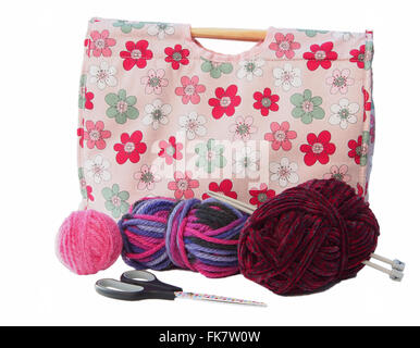 Pink flower patterned knitting/craft bag with knitting needles, and pink, burgundy and multicoloured wool on a white - Stock Photo