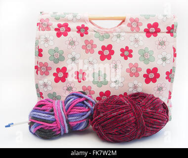 Pink flower patterned knitting / craft bag with knitting needles, burgundy and multicoloured wool on a white background. - Stock Photo