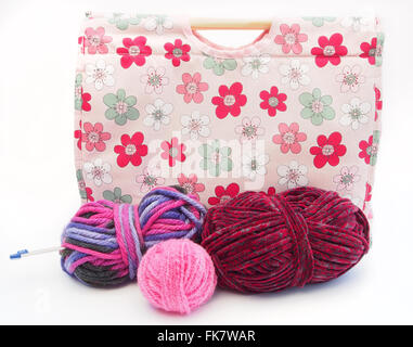 Pink flower patterned knitting / craft bag with knitting needles, and pink, red and multicoloured wool on a white - Stock Photo