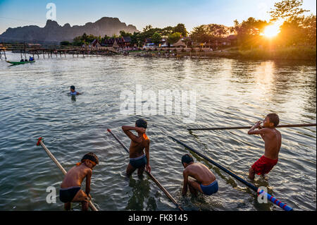 Asia. South-East Asia. Laos. Province of Vang Vieng. Vang Vieng. Boys playing in the Nam Song river at sunset. - Stock Photo