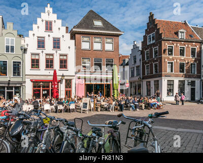 Bicycles and people on outdoor terrace of cafes in Minrebroederstraat in the city of Utrecht, the Netherlands - Stock Photo